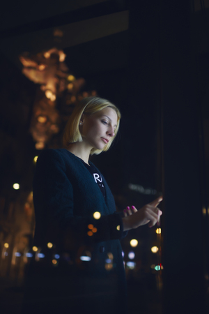 remittances: Half length portrait of a young blonde woman standing front big digital screen with information, attractive female touching digital display of smart modern bus station, hipster girl using atm machine