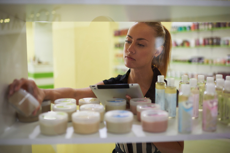 puts: Young beautiful woman seller using touch pad to verify the quality spa goods while standing in pharmacy, female consultant puts plastic bottles with aromatic ingredients in pharmaceutical store Stock Photo