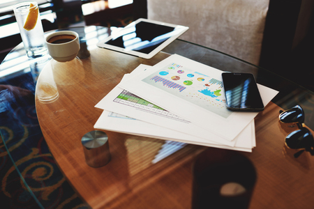 capital gains: Mobile phone and touch pad with blank screen with copy space for your information or content lying near paper documents with schedules of reporting, cell telephone and touch pad on a glass table