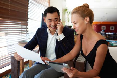 彼の女性のパートナー デジタル タブレットを使用しながら携帯電話で話している近代的なオフィス インテリア、アジアのビジネスマンに坐ってい