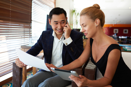 Two young professional bankers working together on joint projects while sitting in modern office interior, Asian businessman talking on mobile phone while his female partner using digital tablet