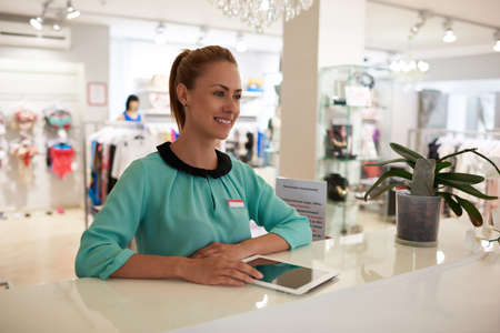 wealthy lifestyle: Portrait of a young female seller with beautiful smile using touch pad for check goods while standing in brandy shop, happy woman consultant working on digital tablet during job in fashion boutique Stock Photo