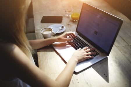 Levágott lövés tekintettel a fiatal nő, dolgozó, laptop számítógép, miközben ült a modern kávézó belső, női szabadúszó segítségével nettó könyv távolság munka során reggel reggeli modern kávézó