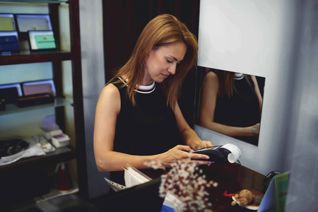 Portrait of an attractive woman consultant introduces PIN code credit in card reader machine while standing in shop interior, young female seller conducts payment for goods during work day in boutique