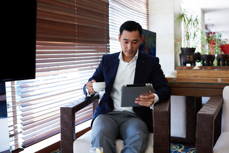 financier: Young confident man professional banker in corporate clothes enjoying coffee while read latest news on digital tablet, prosperous male financier using touch pad while sitting in modern interior Stock Photo