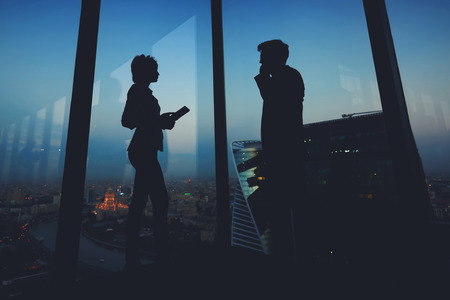 ceos: Silhouette of a two young business people standing in modern interior near big window, man entrepreneur having mobile phone conversation while his woman partner using digital tablet during work break Stock Photo