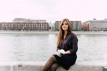 座っている若いきれいな女性の肖像画を奪う美しい川の桟橋でコーヒー カップ秋の日彼女のレクリエーション時に屋外歩行後リラックスしたトレン 写真素材