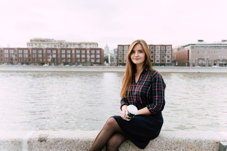 Portrait of young pretty woman sitting with take away cup of coffee on a river pier in beautiful autumn day, charming female with trendy look relaxing after walking outdoors during her recreation time Banco de Imagens - 59203894