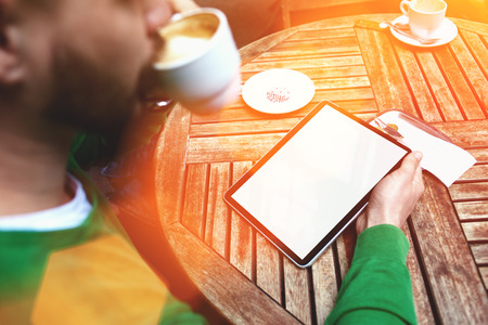 electronic book: Cropped image of man enjoying cup of coffee while using touch pad with blank copy space screen for your text message or promotional content, young male reading electronic book while sitting in cafe Stock Photo