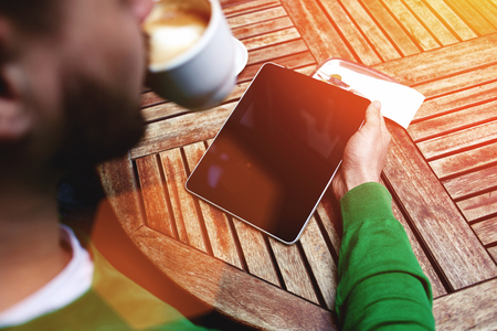 electronic pad: Rear view of young male freelancer drinking hot coffee and working on digital tablet in cafe outdoors, smart business man reading last news or electronic book touch pad with copy space screen for
