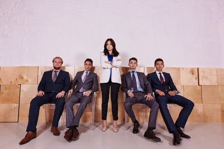 ceos: Full length portrait of a multi ethnic group of a successful leadership dressed in corporate clothes posing inside, confident colleagues in formal wear resting after briefing while sitting in hallway Stock Photo