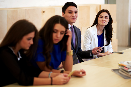 economists: Young colleagues using smart phone while waiting for the beginning of the conference, multi ethnic group of a intelligent international students working on cell telephone during break between lectures Stock Photo