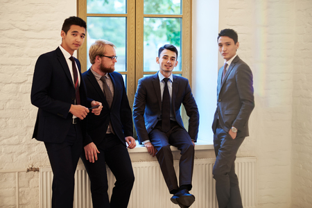 ceos: Little group of a young successful business people dressed in luxury suits resting after briefing, confident lawyers in corporate clothes having work break while standing in modern office hallway Stock Photo