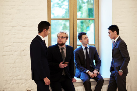 purposeful: Group of young smart entrepreneurs dressed in corporate clothes discuss ideas after business meeting, purposeful bookkeepers in formal wear taking break between work day standing in office hallway Stock Photo