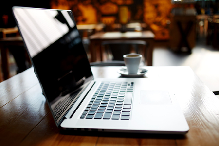 netbook: Open net-book standing in modern bar interior, portable laptop computer with cup of delicious coffee lying on a wooden table in cafe bar indoors, freelance distance work concept, filtered image