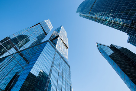 corporate buildings: View from below of a shining modern office buildings in new district, tall skyscrapers against blue sky, business concept of successful industrial architecture, contemporary city constructions Stock Photo