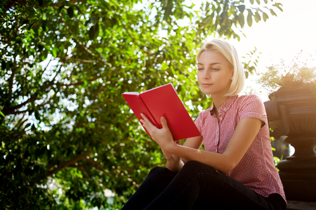 favorite book: Young hipster girl reading her favorite book while she is relaxing in the fresh air during spring weekend,gorgeous blonde female is learning outdoors while sitting in beautiful green park in sunny day