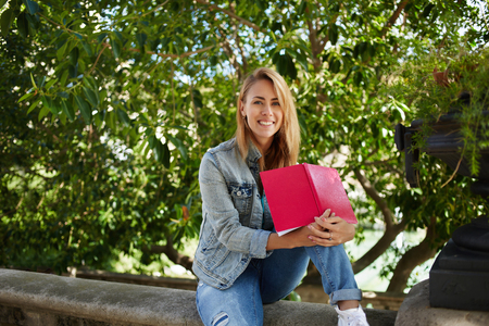 good mood: Smiling charming woman student is sitting with book on a campus while is resting after lectures, cheerful hipster girl in good mood is holding notebook with copy space while she is relaxing outside Stock Photo