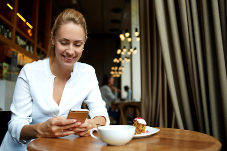 Happy female reading good news on cell telephone during morning breakfast in comfortable cafe-bar interior, smiling hipster girl is chatting in network on smart phone during coffee break in restaurant Foto de archivo
