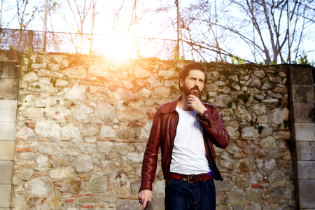 serious face: Bearded hipster man with serious face is thinking about something while standing outdoors against street wall with copy space, stylish brutal male with trendy look walking in urban scene at sunset