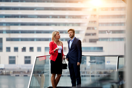 ceos: Two skilled leaders stand outside of company during work break and have serious conversation, male and female successful entrepreneurs are talking about upcoming meeting with international partners