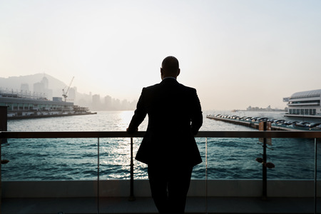 rich life: Back view of a young confident man financier is thinking about something, while is standing outdoors against sea port. Silhouette of male intelligent managing director is resting after hard work day
