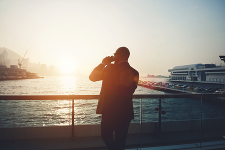 financier: Back view of a young man intelligent financier is drinking take away coffee, while is resting after work day. Silhouette of a male manager is standing outdoors against sea port and sky with sunset Stock Photo