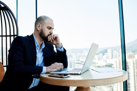 economist: Experienced young businessman looking stressed and tired while sitting at his office desk with laptop computer. Young male economist reading financial news on net-book about falling shares on exchange