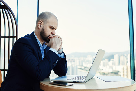 Serious intelligent banker is spending important banking operation via portable laptop computer. Skilled man architect is working on a new project via net-book, while is sitting in office interior