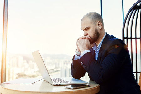 company director: Man intelligent managing director is reading important e-mail letter on laptop computer, while is sitting in modern office interior. Worried economist is analyzing activities of  company via net-book