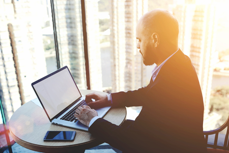 validez: Experimentado hombre comerciante está analizando los mercados financieros a través del ordenador portátil, mientras está sentado en el interior de la oficina moderna. contador calificado de sexo masculino está comprobando la validez de la operación a través de NET-libro