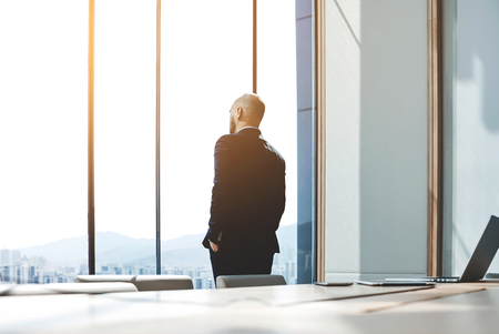 Back view of young confident man leader is resting after business meeting with foreign partners, while is standing near big office window background with copy space for your advertising text message Standard-Bild