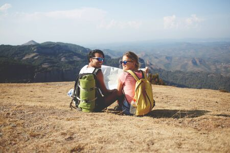 wanderers: Couple of a cheerful man and woman travelers are sitting with map on a high mountain during their joint trip, happy smiling male and female wanderers are enjoying their rest and amazing nature around Stock Photo