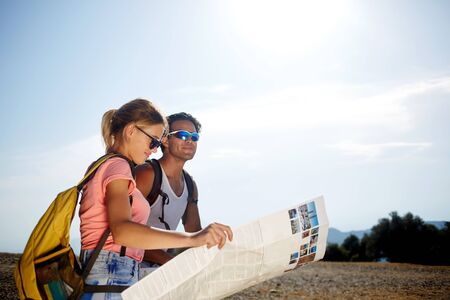 wanderers: Beautiful couple of a wanderers are searching way on location map while standing on mountain hill in sunny day, young female and male tourists are enjoying hike during joint summer adventure overseas