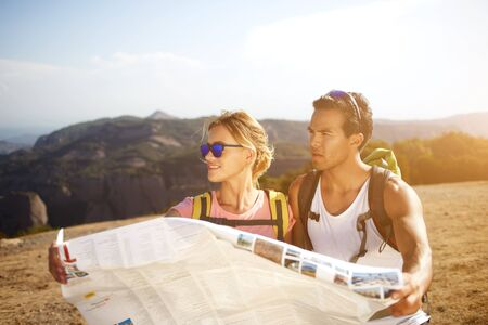 wanderers: Two young wanderers are holding location map while they standing on a high hill in sunny day, male and female backpackers are looking for a new way to continue their hike in rural during summer trip