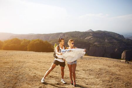 spending full: Full length portrait of beautiful couple of a wanderers are exploring map to continue their trek in mountains, man and woman hikers are spending time together outdoors during their summer adventure Stock Photo