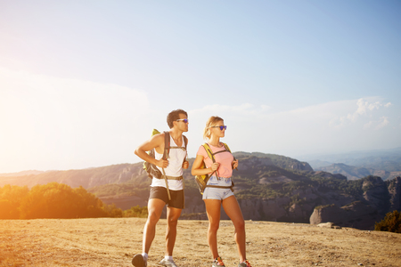 rucksacks: Full length portrait of a young man and woman travelers with rucksacks on backs are admiring wonderful landscape while standing on high mountain in sunny summer day during their joint vacations abroad