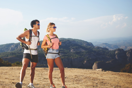 wanderers: Young couple of a hikers are spending time together in the fresh air in beautiful sunny day during their recreation time, man and woman wanderers are enjoying nature view while standing on a mountain Stock Photo