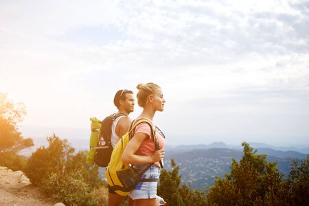 wanderers: Young beautiful woman and man travelers are enjoying hike and beauty nature view during rest in the fresh air, two wanderers are taking break between walking in mountains during their summer adventure