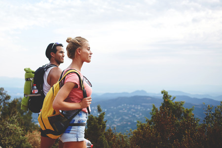 rucksacks: Young man and woman travelers are enjoying amazing nature view during their backpacking, two hikers with rucksacks are resting after active walking in mountains during their summer weekend overseas