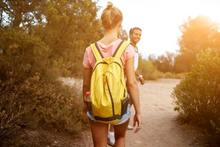wanderers: Back view of a young two travelers are walking in rural during their amazing summer weekend, man and woman wanderers are hiking with rucksacks in mountains during their wonderful adventure overseas Stock Photo