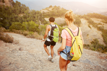 rucksacks: Young man and woman wanderers are walking in mountain during their summer vacation overseas, two hikers with rucksacks on backs are exploring new places during their long awaiting amazing travel