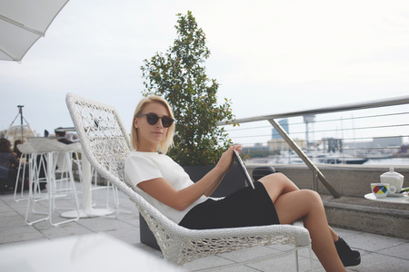 restaurateur: Blonde female with trendy look resting after chat on touch pad,while is relaxing in cafe during vacation in Barcelona. Young hipster girl is fashionable sunglasses and digital tablet is resting in bar