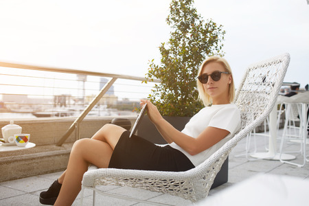 Fashionable woman in stylish sunglasses is relaxing with touch pad in comfortable coffee shop outdoors. Hipster girl is holding portable digital tablet, while is sitting in restaurant in the fresh air