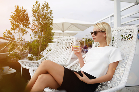 Confident rich woman dressed in trendy clothes is enjoying water with lemon during work on portable touch pad. Young hipster girl is using digital tablet, while she is relaxing in modern restaurant