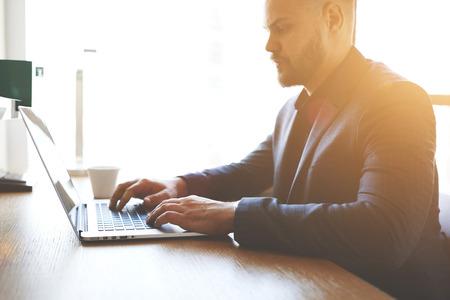 validez: Cerca del hombre comerciante está analizando los mercados financieros a través del ordenador portátil, mientras está sentado en la oficina moderna entre otras. contador calificado de sexo masculino está comprobando la validez de la operación a través de NET-libro Foto de archivo