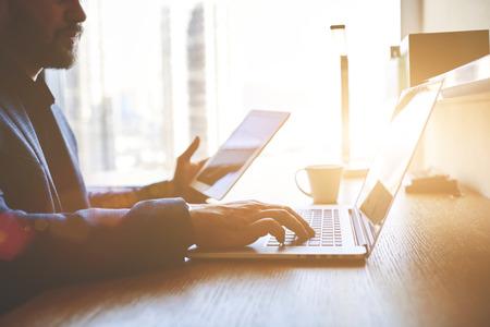 Vértes egy fiatal sikeres üzletember tartja a digitális tábla és keyboarding laptop. Férfi vállalkozó használ munka touch pad és nettó könyv, miközben ül irodai belső