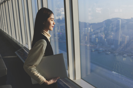 Chinese female successful entrepreneur with laptop computer is standing in modern office interior near skyscraper window with copy space farea for your advertising text message or promotional content