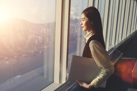 office break: Young woman candidate is holding laptop computer, while standing in office interior and looking out of big window with city view. Female manager with net-book in hand ponder about new business project