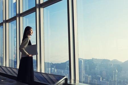 若いアジア経営幹部はラップトップ コンピューター、オフィスでは立って保持している間、シティー ビューの大きな窓の外を見てします。女性マネ